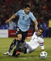Uruguay's Luis Suarez dribbles the ball around Chile's goalkeeper Claudio Bravo in Mendoza